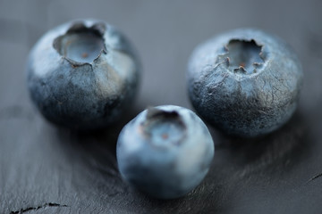 Ripe blueberries over dark wooden background, horizontal shot