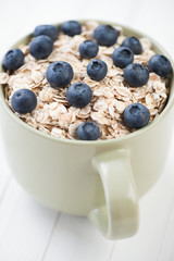 Cereal with fresh blueberries, vertical shot, close-up