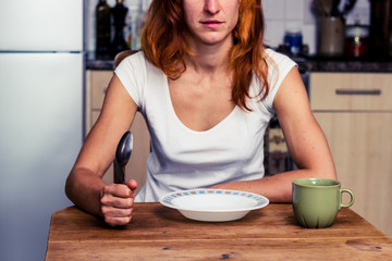 Woman about to have breakfast in kitchen