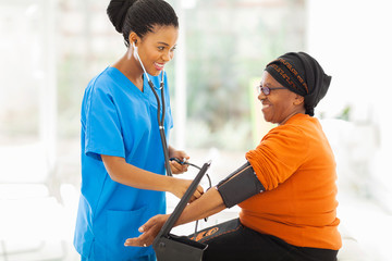 african nurse checking senior patient's blood pressure