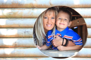 Mother and son peeks through hole at playground