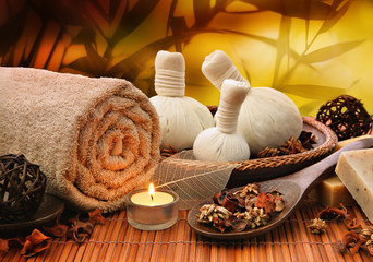 Massage background with rolled towel, spa balls and candlelight