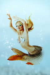 beautiful mermaid girl with fish tail and long blond hair swimmi