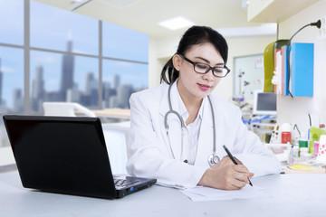 Beautiful doctor write prescription at clinic