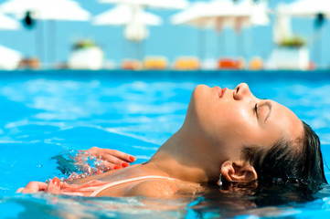 Young woman enjoying water and sun in outdoor swimming pool