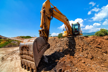 Yellow excavator moving soil and sand  on road construction site