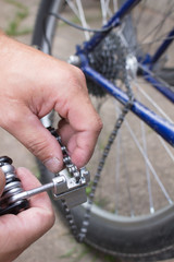 Man changes bicycle chain with special tool