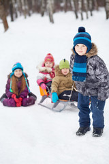 Boy pulls sledges with younger children in winter park