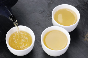 Green tea being poured into cups