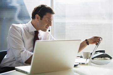 Geschäftsmann sitzt am Schreibtisch, mit Head-Set