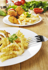 French fries and chicken on the plate on the wooden table