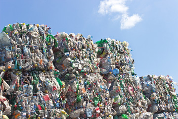 Stack of plastic bottles for recycling against blue sky