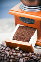 Coffee mill with coffee beans and ground coffee.