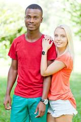 junges verliebtes multikulturelles paar auf einer wiese
