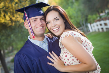 Male Graduate in Cap and Gown and Girl Celebrate