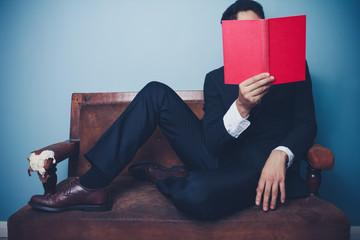 Businessman on sofa is reading