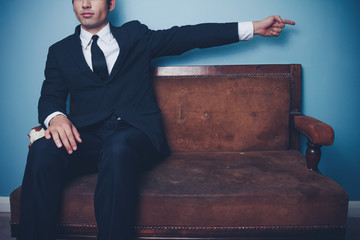 Businessman on sofa pointing right