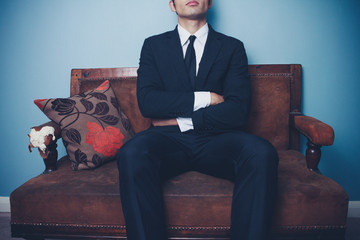 Businessman on sofa in dominant pose