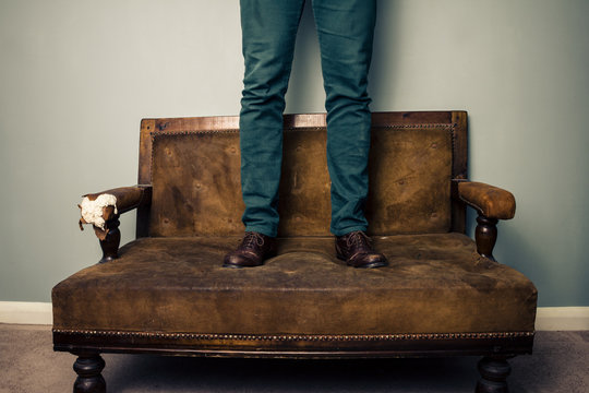 Man wearing shoes standing on sofa