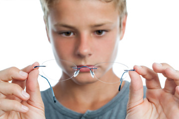 Boy holding glasses in front of face.