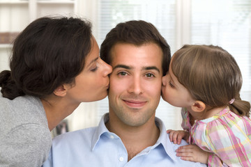 Happy family, mother and daughter kissing father at home