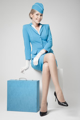 Charming Stewardess Dressed In Blue Uniform And Suitcase On Gray