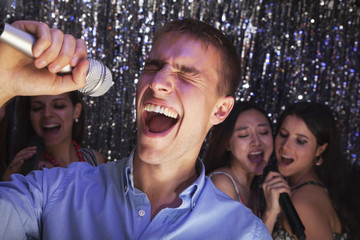 Young man singing into a microphone at karaoke, friends singing in the background