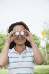 Smiling young woman holding up golf balls in front of her eyes