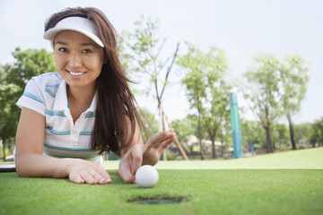 Smiling young woman lying down in a golf course getting ready to flick the ball into the hole