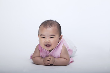Portrait of smiling and laughing baby lying down, studio shot, white background