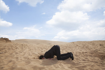 Young businessman kneeling with his head in a hole in the sand