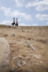 Two young businessmen walking through the desert, in the distance