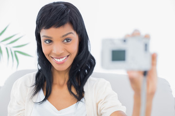 Natural black haired woman in white clothes taking a picture of