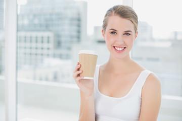 Cheerful cute blonde holding mug of coffee