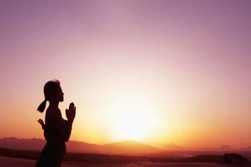 Serene young woman with hands together in prayer pose  in the desert in China, silhouette, profile, sun setting