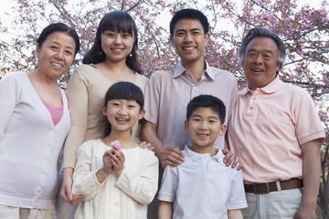 Portrait of a smiling multi-generational family amongst the cherry trees and enjoying the park in the springtime