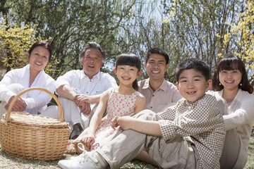 Portrait of a multi-generational family having a picnic and enjoying the park in the springtime