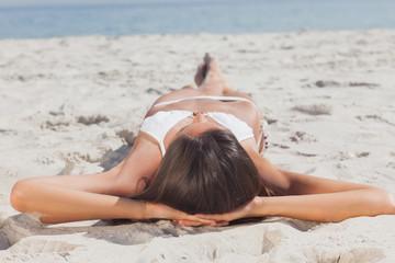 Woman lying on beach in front of ocean