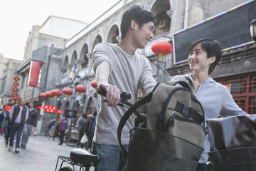 Young man and woman with bicycles and backpacks.