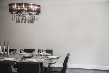 Dining room with modern furniture and chandelier.