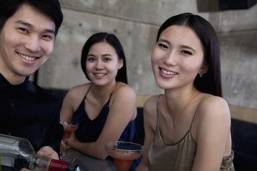 Portrait of young women and bartender at a bar