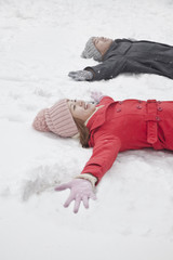 Young couple laying in snow making snow angels