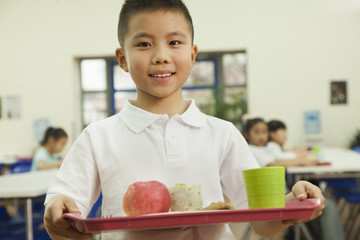 School boy holding food tray in school cafeteria