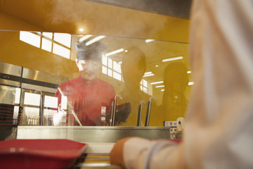 School cafeteria worker serves noodles to students
