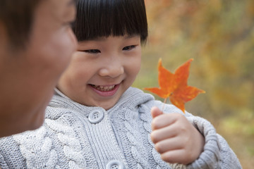 Little girl looking at leaf with her father, close-up, autumn