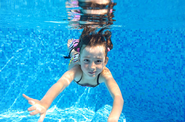 Happy active child swims underwater in pool, kids sport