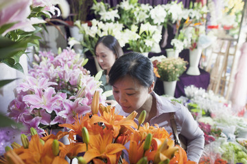 Two Mature women Looking At Flowers In Flower Shop