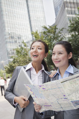 Two young businesswomen with the map looking for location