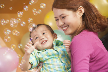 Mother Holding Little Boy While He Plays with Bubbles