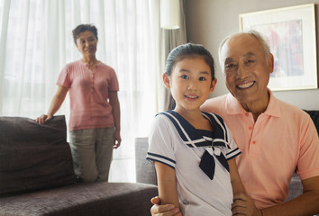 Grandfather holding her granddaughter, grandmother in the background